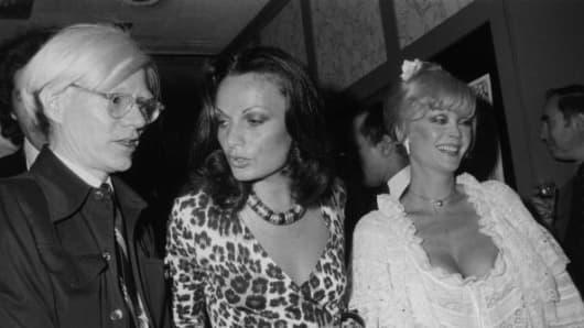 14th May 1974: Left to right: Artist Andy Warhol (1928 - 1987), fashion designer Diane von Furstenberg, and actor Monique Van Vooren. Von Furstenberg is wearing one of her own designs, a leopard print wrap-dress.