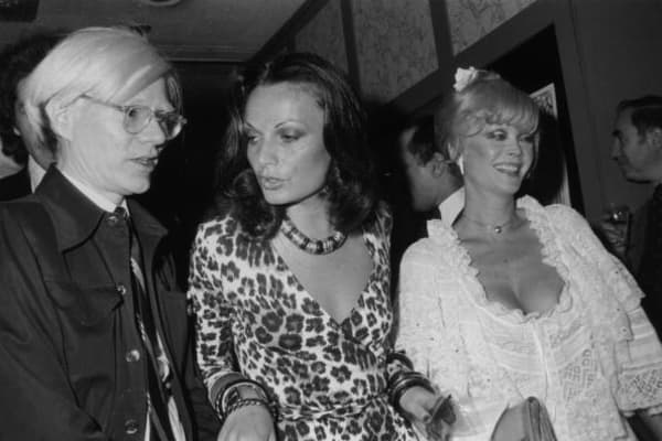 14th May 1974: Left to right: Artist Andy Warhol (1928 - 1987), fashion designer Diane von Furstenberg, and actor Monique Van Vooren. Von Furstenberg is wearing one of her own designs, a leopard print wrap-dress.