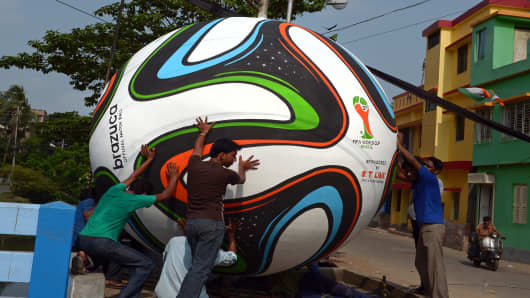 Indian soccer fans and labourers install a giant replica of the football to be used in the FIFA World Cup 2014 in Brazil, on a street corner in Kolkata.