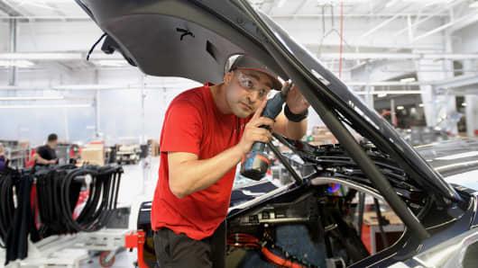 A worker installs interior trim on a Telsa Model S sedan.