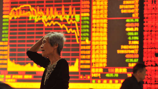 An investor watches the electronic board at a stock exchange hall on May 28, 2015, in Fuyang, China. Chinese shares dropped sharply on Thursday, with the benchmark Shanghai composite index falling 321.45 points, or 6.5 percent, to close at 4,620.27.