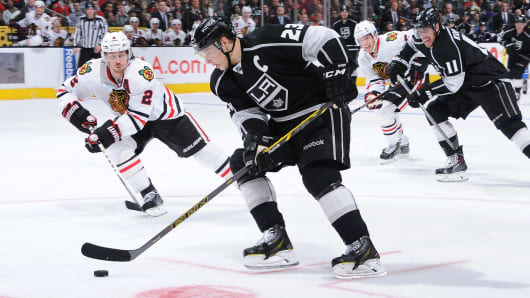 Dustin Brown of the Los Angeles Kings handles the puck against Duncan Keith of the Chicago Blackhawks at Staples Center on Jan. 28, 2015, in Los Angeles.