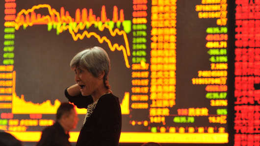 stock investor gestures as she checks share prices at a security firm in Fuyang, east China's Anhui province on May 28, 2015. Chinese stocks plunged 6.5 percent on May 28 on concerns over tight liquidity and stricter requirements for margin trading, after closing at a more than seven-year high the previous day, dealers said.