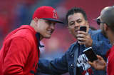 Mike Trout #27 of the Los Angeles Angels takes a picture with fans