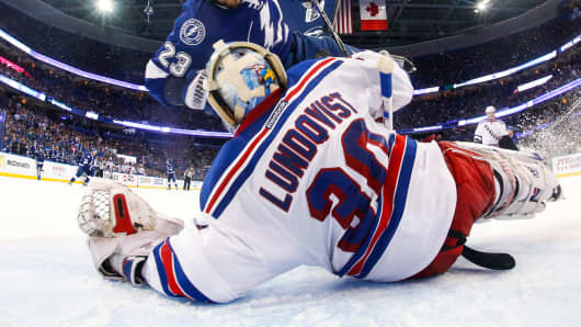 J.T. Brown #23 of the Tampa Bay Lightning skates into goalie Henrik Lundqvist #30 of the New York Rangers during the second period in Game Six of the Eastern Conference Final during the 2015 NHL Stanley Cup Playoffs at the Amalie Arena on May 26, 2015 in Tampa, Florida.
