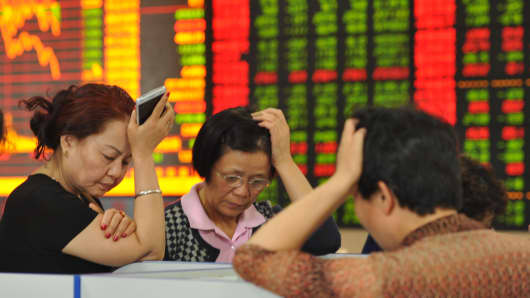 Investors watch computer screens at a stock exchange hall in Fuyang, China.