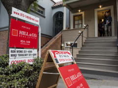 Potential home buyers exit a home for sale in the Castro district of San Francisco.