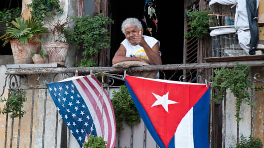 A Cuban gives the thumbs up from his balcony decorated with the US and Cuban flags in Havana, on January 16, 2015.