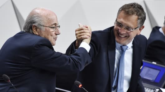 FIFA President Sepp Blatter (L) makes a symbolic handshake with FIFA general secretary Jerome Valcke during the 65th FIFA Congress in Zurich on May 29, 2015.