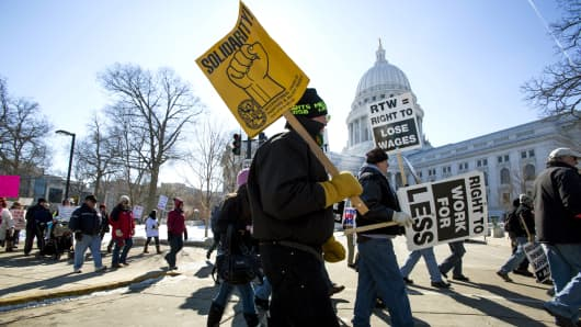 """Protesters march around the Capitol after participating in a rally against a """"right-to-work"""" proposal, on Saturday, Feb. 28, 2015, in Madison, Wis."""