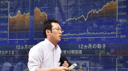 A pedestrian passes in front of a stock market display in Tokyo, May 28, 2015.