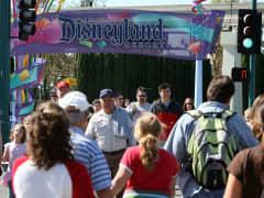Pedestrians walk near the entrance to Disneyland Resort in Anaheim, Calif.