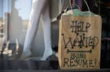 A help wanted sign sits in the window of a small business clothing store.