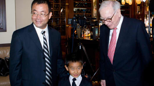 Chinese hedge fund manager Zhao Danyang and his son stand with Warren Buffett after placing the winning bid in a charity auction for lunch with the billionaire investor in 2009.