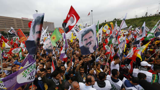 Supporters of the Pro-Kurdish Peoples' Democratic Party (HDP) wave flags with a picture the jailed Kurdish militant leader Abdullah Ocalan, during a gathering to celebrate their party's victory during the parliamentary election, in Istanbul, Turkey, June 8, 2015.