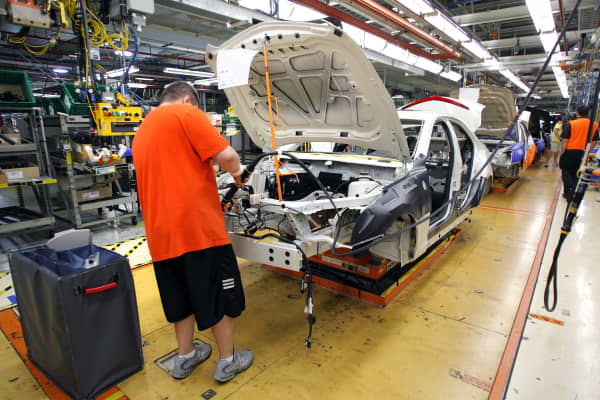 A General Motors' worker assembles a 2013 Cadillac ATS on the assembly line at the General Motors Lansing Grand River Assembly Plant in Lansing, Michigan.