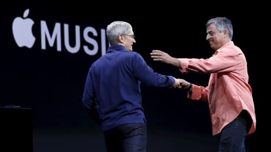 Apple CEO Tim Cook, left, greets senior vice president of internet services and software Eddy Cue during his keynote address at the Worldwide Developers Conference in San Francisco, June 8, 2015.