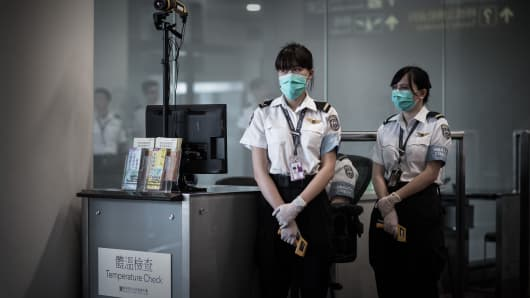 Airport personnel wait for passengers to check their temperature at the Hong Kong international airport.