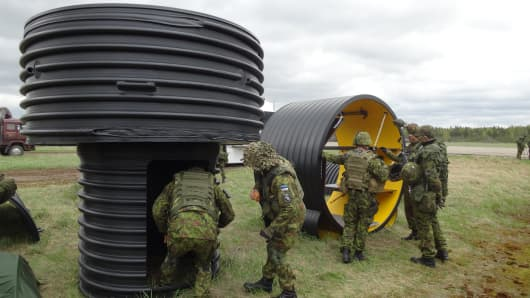 Military personnel inspect segments from a Terramil bomb shelter.