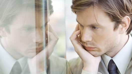 Pensive man reflected in window