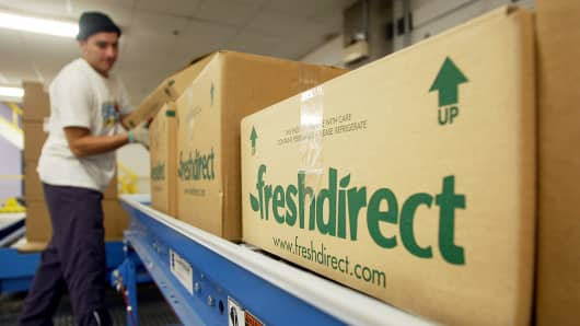 A worker handles finished grocery boxes ready for delivery at the FreshDirect online grocery service warehouse in New York.