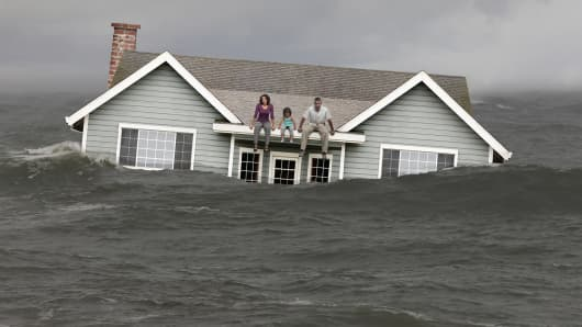 Family sitting on roof of underwater home