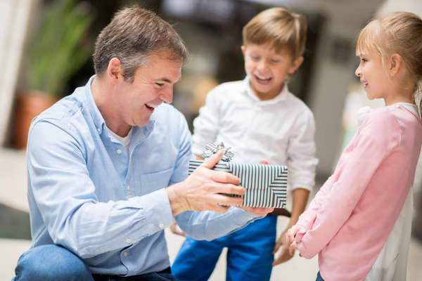 Man receiving Father's Day gift from children