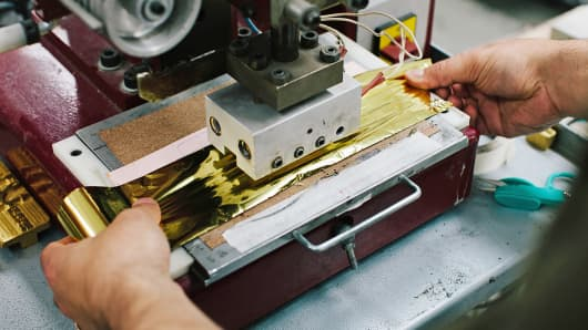 An employee uses a stamping machine to create the gold labeling of a Rebecca Minkoff handbag at the Baikal manufacturing facility in New York.