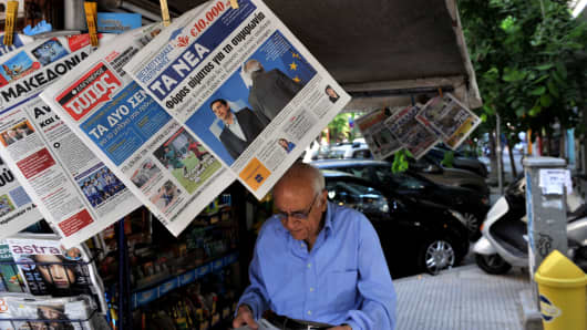 A man reads a newspaper next to a kiosk in Thessaloniki on 4 June, 2015.