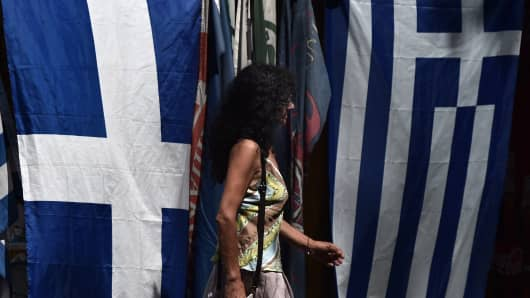 A woman walks past Greek flags hanging on a kiosk in central Athens on June 15, 2015.