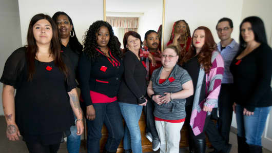 "Makenzie Vasquez, from left, Pamala Hunt, Latonya Suggs, Ann Bowers, Nathan Hornes, Ashlee Schmidt, Natasha Hornes, Tasha Courtright, Michael Adorno and Sarah Dieffenbacher, pose for a picture in Washington, March 30, 2015. Former and current college students calling themselves the ""Corinthian 100"" say they are on a debt strike and refuse to pay back their student loans."