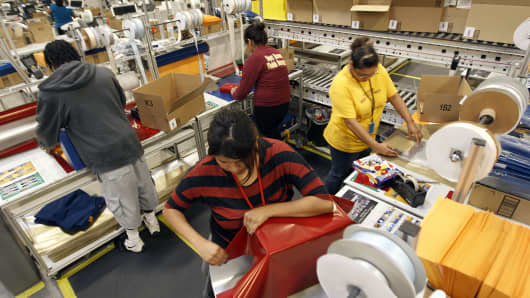 Workers gift-wrap orders for delivery at Amazon's distribution center in Phoenix, Arizona.