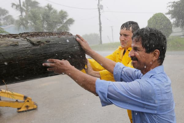 Port Lavaca city worker Oscar Quinenilla, front right, helps clear debris from a marina area as Tropical Storm Bill makes landfall, Tuesday, June 16, 2015, in Port Lavaca, Texas.