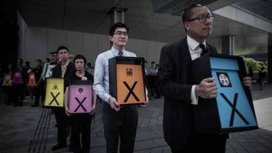 Pro-democracy campaigners display placards symbolising a vote against the government's controversial electoral roadmap
