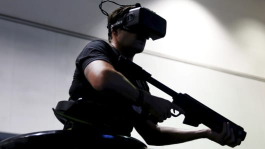 A man plays a war video game with an Oculus virtual reality headset at the Electronic Entertainment Expo, or E3, in Los Angeles, June 16, 2015.