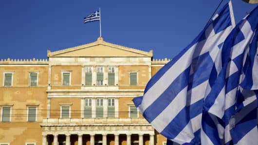 Greek flags fly in front of the parliament in Athens.
