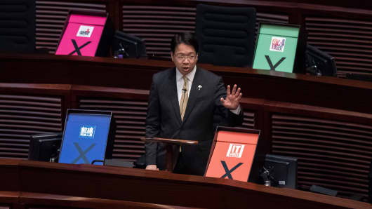 Hong Kong pro-democracy lawmaker Charles Mok addresses the city's legislature next to placards symbolizing a vote against the government's controversial electoral roadmap, in Hong Kong on June 18, 2015.