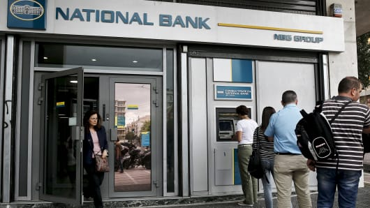 People line up at an ATM machine outside a National Bank branch in Athens, Greece.