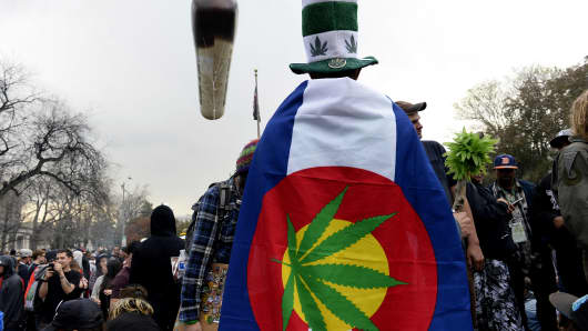 Pot smokers partake in smoking marijuana at exactly 4:20 during the annual 420 celebration in Lincoln Park near the State Capitol in Denver, Colorado, on April 20, 2015.
