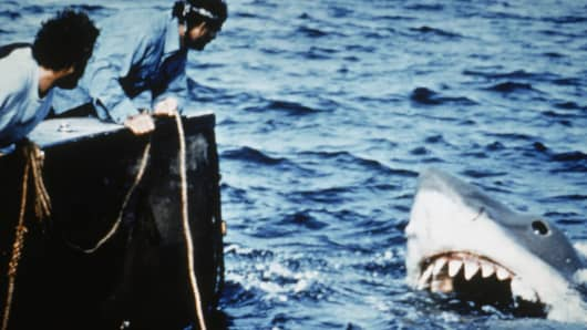 Actors Richard Dreyfuss (L) and Robert Shaw lean off the back of their boat, holding ropes as they watch the giant Great White shark emerge from the water in a still from the film, 'Jaws'.