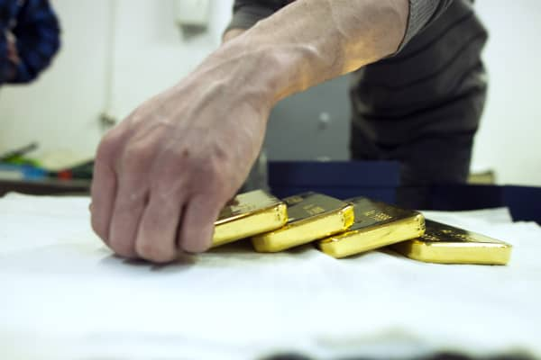 A worker arranges newly cast gold bullion bars.