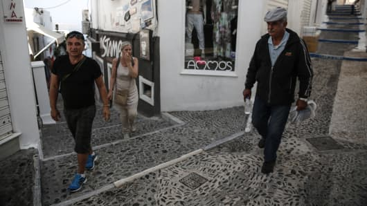 A local resident, right, passes visiting tourists on a cobbled backstreet in Fira town on the island of Santorini, Greece, in May 2015.