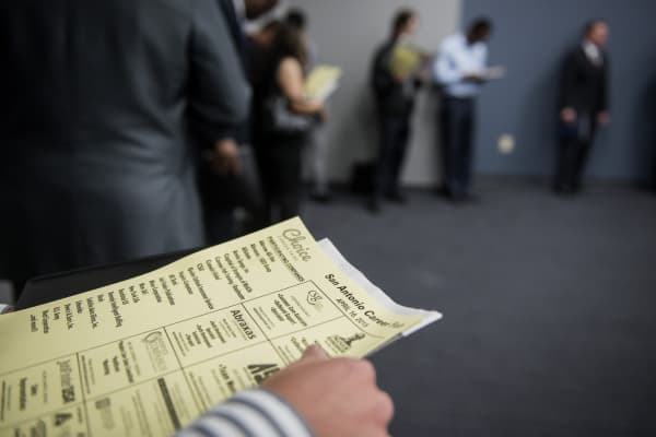 A job seeker holds an application while waiting in line to enter the Choice Career Fair in San Antonio, Texas.