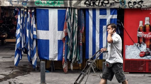A man passes by Greek flags on June 22, 2015 in Athens, Greece.
