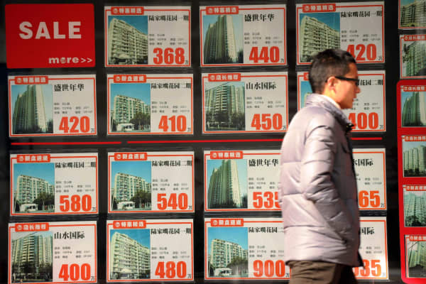 A man walking in front of a real estate agent's window in Shanghai.