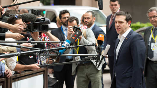 Greek Prime Minister Alexis Tsipras speaks to journalists as he arrives for a emergency summit with European Union leaders in Brussels on Thursday, June 25, 2015.