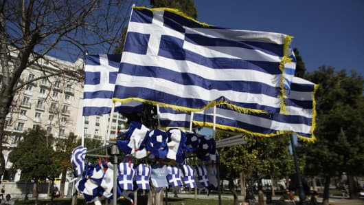 Greek national flags fly above Greek-themed hats at Syntagma square in Athens, Greece.