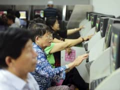 Investors look at computer screens showing stock information at a brokerage house in Qingdao, Shandong
