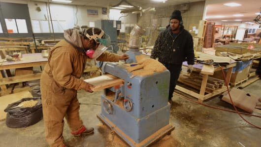 Workers prep reclaimed wood to be used for kitchen butcher blocks and tables at the Reclaim Detroit milling workroom in Detroit.