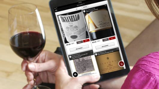Woman holding tablet with Drync app and glass of wine